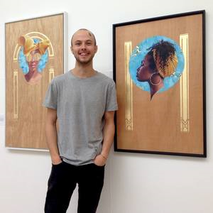 Brook Tate standing next to two of his paintings