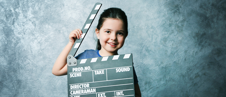 A young girl holding a clapperboard and smiling on a blue-grey background