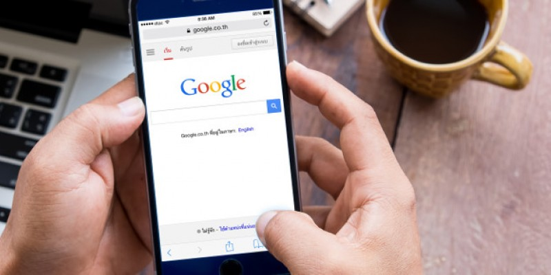 A mobile phone with a Google search engine page open on it