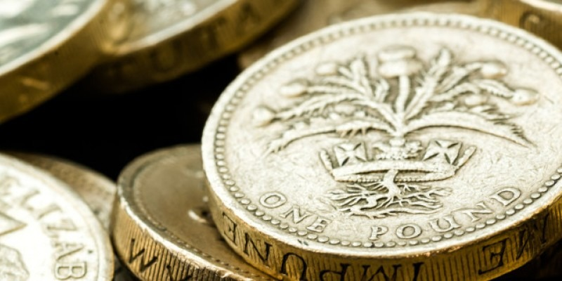 A pound coin with a pile of pound coins in the background