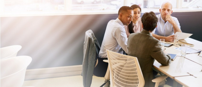 Four people in business clothes sitting around a table