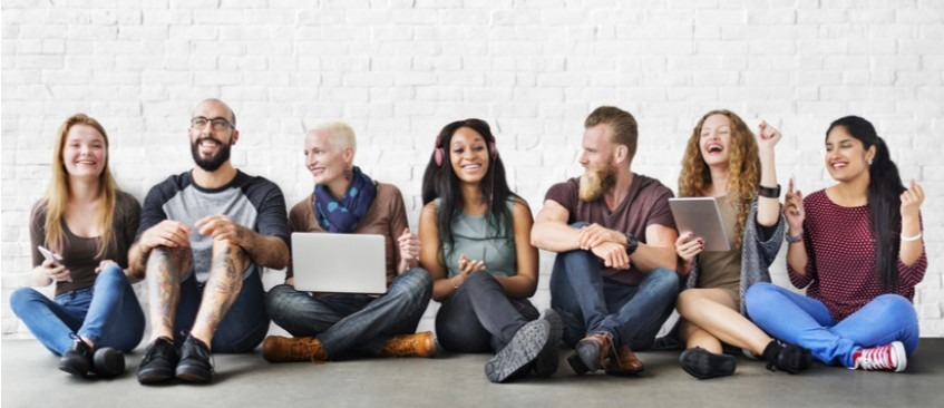 A diverse group of people sat on the floor with a white brick background behind them