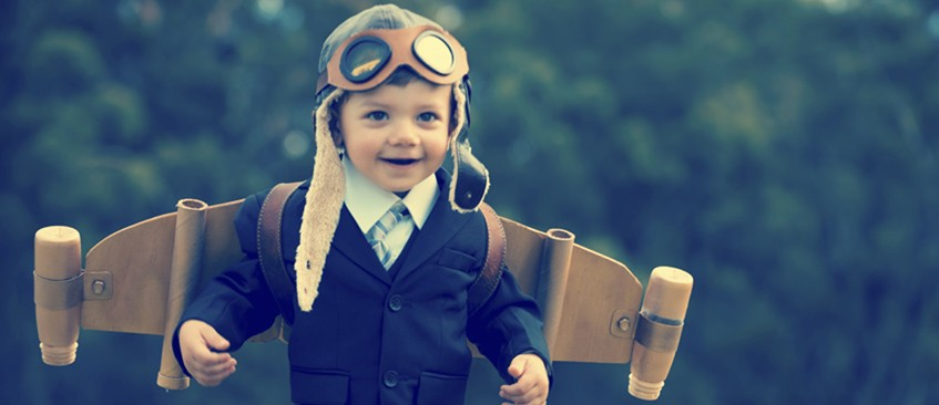 innovate2succeed with a little boy in a suit wearing homemade plane wings and leather pilot cap skull and goggles