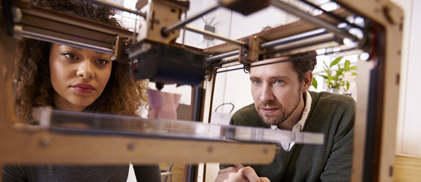 Research and development man and woman looking closely at a 3d printer
