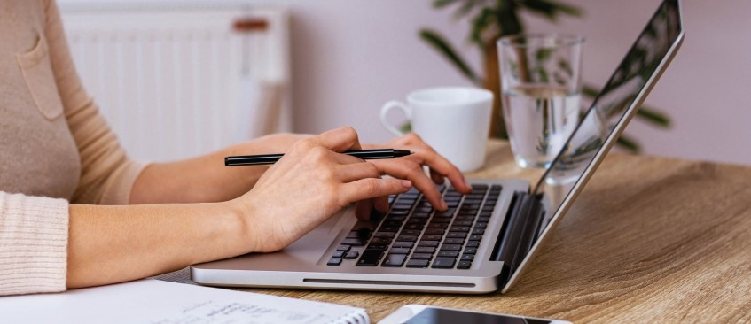 Women's hand typing on laptop