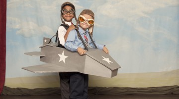 Finding international partners - boys in a homemade plane pretending to fly in a theatre with red curtains and a sky background