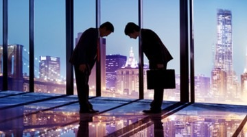 Two Asian men bowing in an office building at night with a skyline of New York in the background